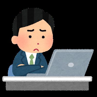 パソコンを見つめながら悩んでいる会社員